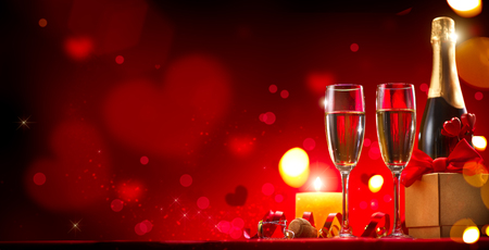 Valentines Day romantic dinner. Champagne, candles and gift box over holiday red background