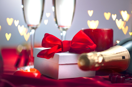 Valentine's Day romantic dinner. Champagne, candles and gift box over holiday background Stock Photo