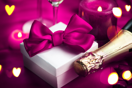 Valentines Day romantic dinner. Champagne, candles and gift box over holiday purple background Stock Photo