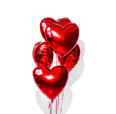 Valentine's Day. Air balloons. Bunch of red heart shaped foil balloons isolated on white background 스톡 콘텐츠