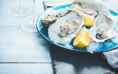 Fresh oysters close-up on blue plate, served table with oysters, lemon and champagne in restaurant. Gourmet food Stock Photo