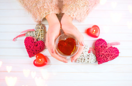 St. Valentine's Day. Young woman hands holding heart shaped tea cup over wooden background. Love concept. Top view