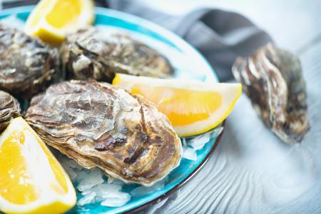 Close-up fresco das ostras na placa azul, tabela servida com ostras, limão no restaurante. Comida gourmet