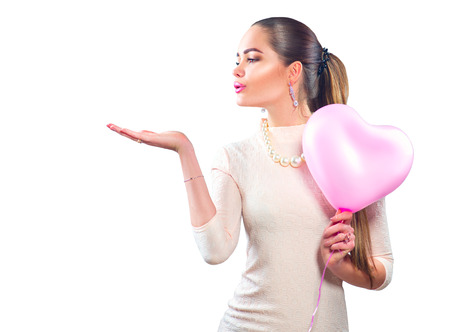 Valentine's day. Beauty girl with pink heart shaped air balloon pointing hand, isolated on white background