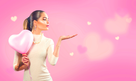 Valentines day. Beauty girl with pink heart shaped air balloon pointing hand, blows hearts on pink background