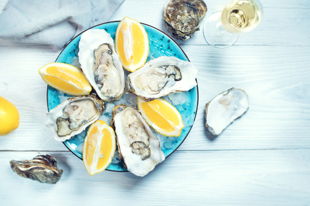 Fresh oysters close-up on blue plate, served table with oysters, lemon and champagne in restaurant. Gourmet food Standard-Bild