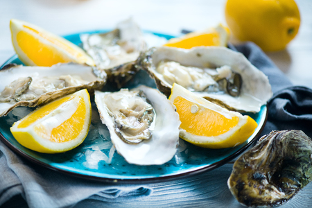Fresh oysters close-up on blue plate, served table with oysters, lemon in restaurant. Gourmet food Stock Photo