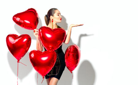 Valentines Day. Beauty girl with red heart shaped air balloons having fun, isolated on white background Stock Photo