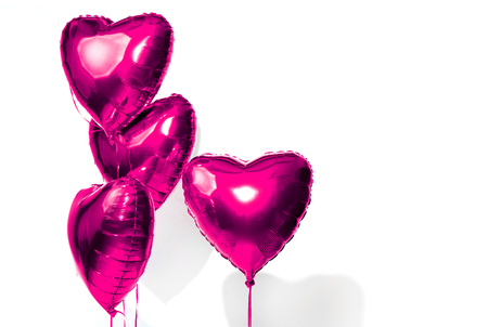 Valentines Day. Air balloons. Bunch of purple heart shaped helium balloons isolated on white background Stock Photo