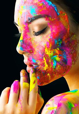 Beauty-Modell Mädchen mit bunten Farbe auf ihrem Gesicht . Porträt der schönen Frau mit flüssigen Farbe isoliert auf schwarz Standard-Bild - 94971037