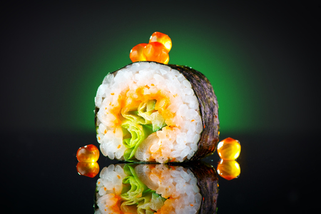 Sushi roll over black background. Sushi roll with tuna, vegetables, flying fish roe and caviar closeup. Japanese food Stock Photo