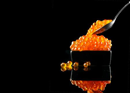 Caviar en una cuchara. Caviar de salmón en un recipiente sobre fondo negro. Primer plano de caviar de trucha