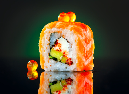 Sushi roll over black background. California sushi roll with salmon, vegetables, flying fish roe closeup. Japanese food Stock Photo