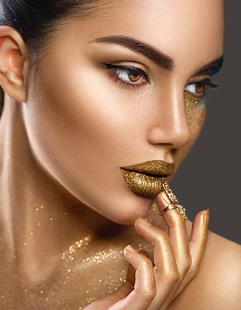 Makijaż sztuki mody. Portret kobiety uroda ze złotą skórą. Błyszczący makijaż profesjonalny Glamour