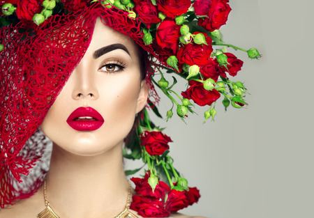 Beauty model girl with red roses flower wreath and fashion makeup. Flowers hairstyle 写真素材