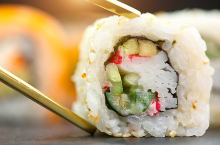 Sushi rolls. Japanese food in restaurant. Sushi roll set california with salmon, vegetables, flying fish roe and caviar closeup Stock Photo