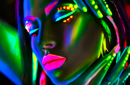 Fashion model woman in neon light. Portrait of beautiful model girl with colorful fluorescent makeup Foto de archivo