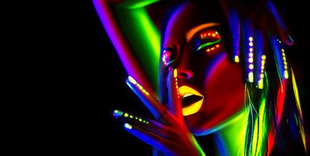 Fashion model woman in neon light. Portrait of beautiful model girl with colorful fluorescent makeup Archivio Fotografico