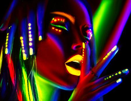Mujer modelo de moda en luz de neón. Retrato de muchacha hermosa modelo con maquillaje fluorescente colorido