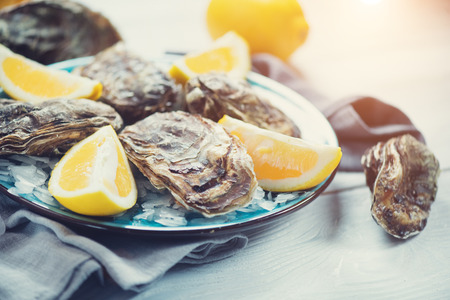 Fresh oysters close-up on blue plate, served table with oysters, lemon in restaurant. Gourmet food Imagens