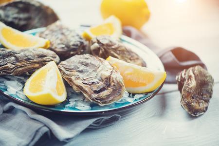 Primer plano de ostras frescas en placa azul, mesa servida con ostras, limón en el restaurante. Comida gourmet