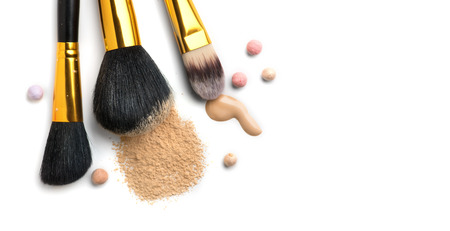 Cosmetic liquid foundation or cream, loose face powder, various brushes for apply makeup. Make up concealer smear and powder isolated on a white background. Products for professional face skin makeup Stock Photo