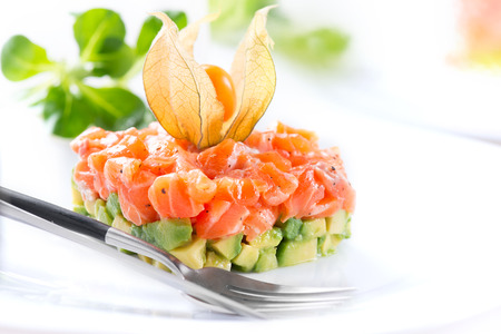 Salmon tartar over white background. Gourmet Food. Starter. Healthy dinner Фото со стока