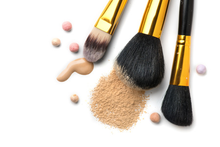 Cosmetic liquid foundation or cream, loose face powder, various brushes for apply makeup. Make up concealer smear and powder isolated on a white background. Products for professional face skin makeup Archivio Fotografico