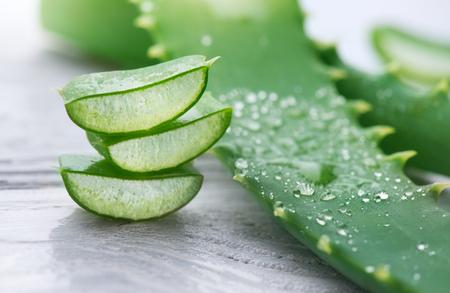 Aloë Vera close-up. Gesneden Aloevera natuurlijke organische vernieuwingscosmetica, alternatieve geneeskunde. Organisch huidverzorging concept. Op witte houten achtergrond Stockfoto