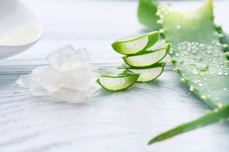 Aloe Vera gel closeup. Sliced Aloevera natural organic renewal cosmetics, alternative medicine. Organic skincare concept. On white wooden background Banco de Imagens