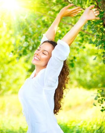 Hermosa joven disfrutando de la naturaleza al aire libre. Feliz y sonriente niña morena con una sonrisa saludable relajante en el parque de verano Foto de archivo