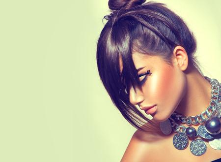 Fashion beauty girl. Gorgeous brunette woman portrait. Stylish fringe haircut and makeup. Sexy glamour girl