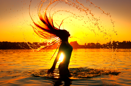 Beauty model girl splashing water with her hair. Girl silhouette over sunset sky. Swimming and splashing on summer beach over sunset