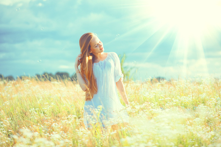 Beauty girl outdoors enjoying nature. Beautiful teenage model girl with healthy long hair in white dress standing on the summer field