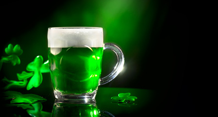 St. Patricks Day. Green beer pint over dark green background, decorated with shamrock leaves. Traditional Irish festival