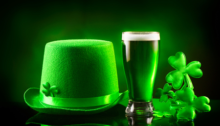 St. Patricks Day. Green beer pint and leprechaun hat over dark green background, decorated with shamrock leaves. Traditional Irish festival