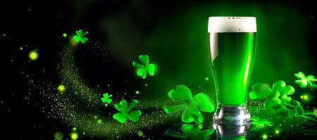 Dzień Świętego Patryka. Zielony kufel piwa na ciemnozielonym tle, ozdobiony liśćmi koniczyny. Tradycyjny festiwal irlandzki