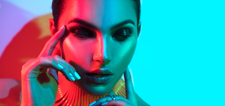 Fashion model woman in colorful bright lights with trendy makeup and manicure posing in studio Reklamní fotografie