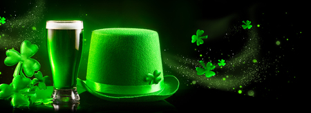 St. Patrick's Day. Green beer pint and leprechaun hat over dark green background, decorated with shamrock leaves. Traditional Irish festival