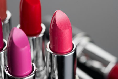 Lipstick. Professional makeup and beauty concept. Fashion pink lipsticks over black background Stock Photo