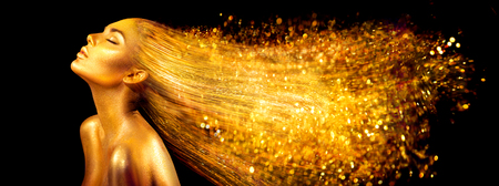 Fashion model woman in golden bright sparkles. Girl with golden skin and hair portrait closeup. Holiday glamour shiny professional makeup on black Foto de archivo