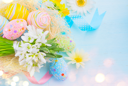 Easter background. Colorful eggs with decorations over blue wooden background, border design in pastel colors