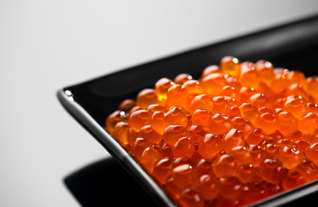 Caviar. Salmon caviar in a bowl over black background. Closeup trout caviar