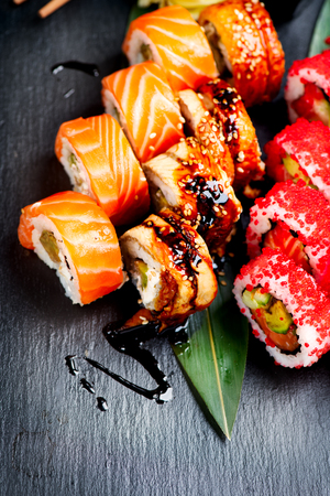 Sushi rolls closeup. Japanese food in restaurant. California sushi roll set with salmon, eel, vegetables and flying fish caviar on black slate background