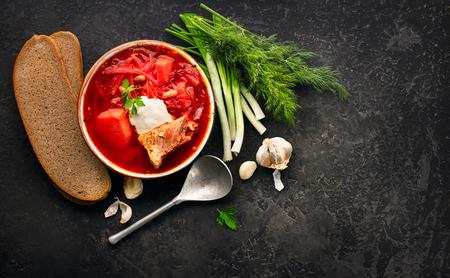 Traditional Ukrainian russian borscht. Plate of red beet root soup borsch on black rustic table. Beetroot soup top view. Traditional Ukrainian cuisine