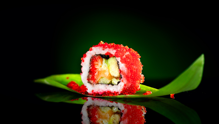 Sushi roll closeup. Japanese food in restaurant. Roll with salmon, eel, vegetables and flying fish caviar on black background Stock Photo