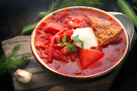 Traditional Ukrainian russian borscht. Plate of red beet root soup borsch on black rustic table. Beetroot soup. Traditional Ukrainian cuisine