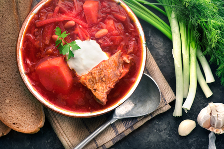 Traditional Ukrainian russian borscht. Plate of red beet root soup borsch on black rustic table. Beetroot soup top view. Traditional Ukrainian cuisine Stock Photo - 98616632