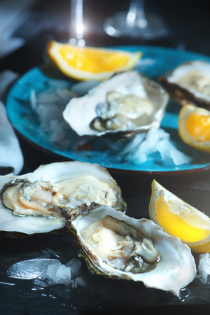 Fresh oysters closeup on blue plate, served table with oysters, lemon in restaurant. Gourmet food Stockfoto