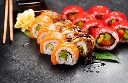 Rollos de sushi de cerca. Comida japonesa en restaurante. Rollo con salmón, anguila, verduras y caviar de pez volador sobre fondo de pizarra negra